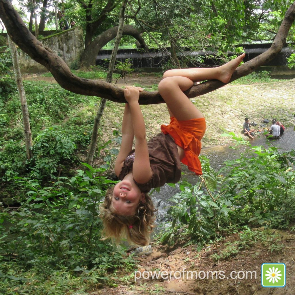 Young girl playing in tree